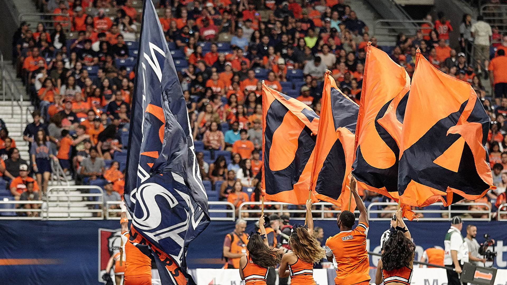 UTSA cheerleaders and flags at a home football game in the Alamodome